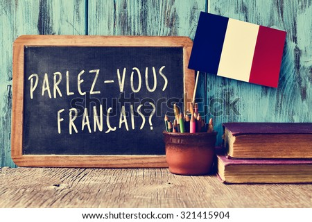 a chalkboard with the question parlez-vous francais? do you speak french? written in french, a pot with pencils and the flag of France, on a wooden desk - stock photo