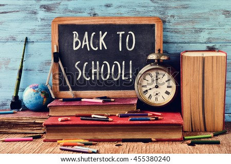 a chalkboard with the text back to school, some old books, an old clock, some pencil crayons and other old stationery, on a rustic wooden surface, against a blue wooden background - stock photo