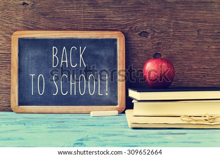 a chalkboard with the text back to school written in it, a piece of chalk, and a red apple on a pile of books, on a blue rustic wooden table, cross processed - stock photo