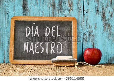 a chalkboard with the text dia del maestro, teachers day written in Spanish, a piece of chalk, an eraser and a red apple on a rustic wooden table, with a retro effect - stock photo