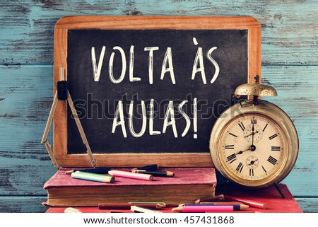 a chalkboard with the text volta as aulas, back to school in portuguese, some old books, an old clock, a compass and some pencil crayons of different colors, against a blue wooden background - stock photo