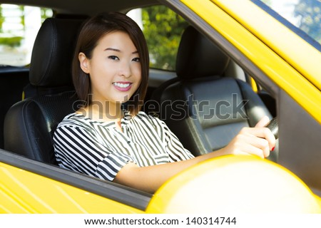 A charming Asian lady driving a yellow car. - stock photo