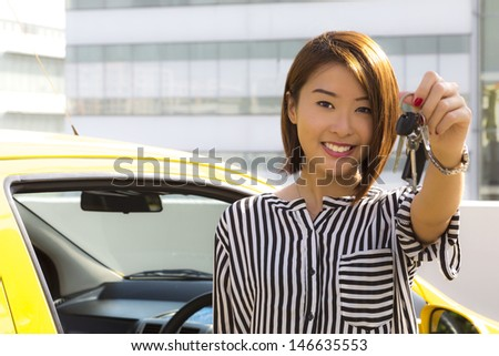 A charming Asian lady standing in front of her car showing her car keys.
