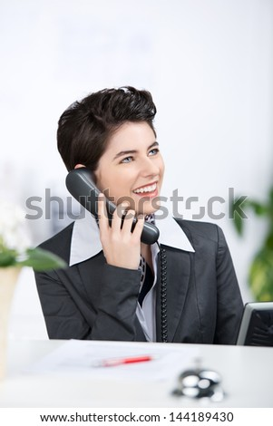 A charming female business executive sitting on her desk, smiling and talking on phone.