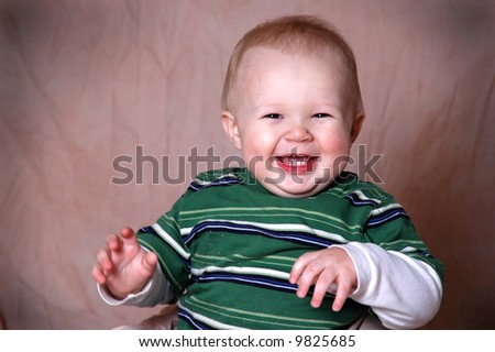 A charming portrait of a baby boy.  He is 1 year old in this series. - stock photo