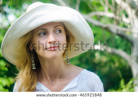A charming portrait of a cheerful woman in a white hat in the woods