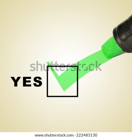 a check mark drawn with a green marker pen on a checbox with the word yes - stock photo