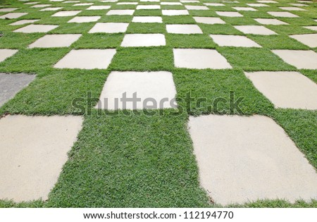 A checker matrix of grass and rustic clay tile in an outdoor park. - stock photo