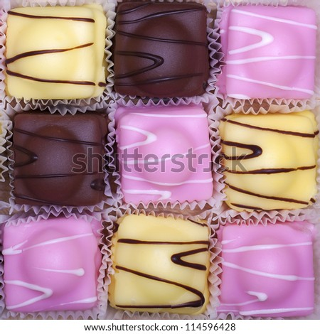 A checkerboard of fancy fondant cakes in pink, yellow and brown. - stock photo