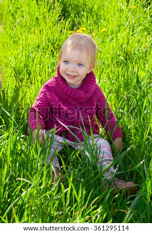 A cheerful baby girl sitting in the grass on the lawn - stock photo