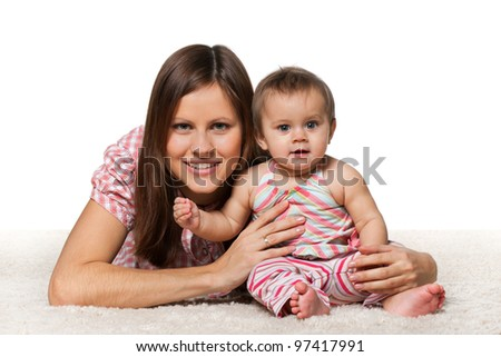 A cheerful baby girl with her smiling mother on the white carpet; isolated on the white background - stock photo