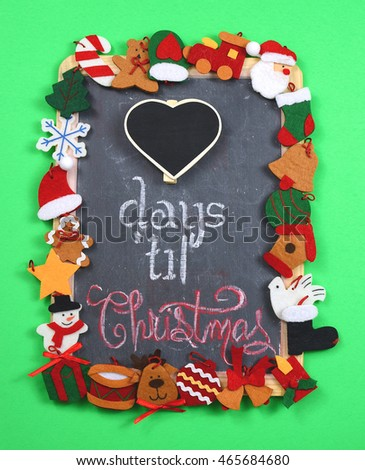 A cheerful border of Christmas themed felt shapes frame a dusty blackboard on a green background. An extra layer of slate is added in a heart shape that is blank for how many days until Christmas