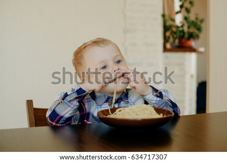 A cheerful boy of two years eating spaghetti with his hands at home in the kitchen