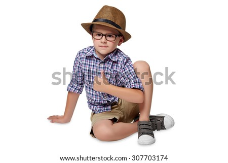 A cheerful boy sits on the floor and holds his thumb up against the white background. - stock photo