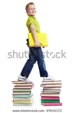 A cheerful boy with a book walking on two heaps of books - stock photo