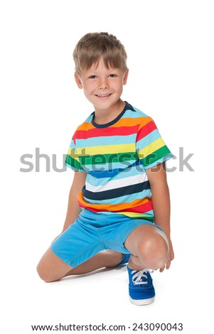 A cheerful fashion little boy sits on the white background