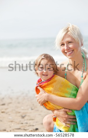 A cheerful girl in a towel and her smiling  mother at the beach - stock photo