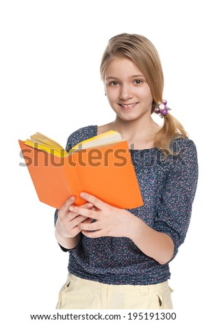 A cheerful girl reads a book against the white background - stock photo