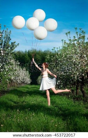 A cheerful girl running and jumping laughing in a blossoming garden with a bunch of white balloons in the apple garden