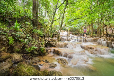 A cheerful/happy/positive Asian hiker is happily standing with her arms stretch out at waterfalls in a tropical rain forest. Huay Mae Khamin Falls, Sri Nakharin National Park, Kanchanaburi, Thailand