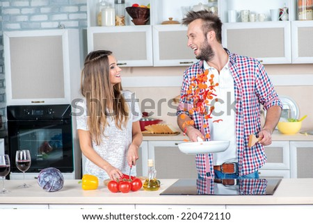 A cheerful joint cooking. Young and beautiful couple in love cooking meals in the kitchen and look at each other while standing in the kitchen and throw the food in the pan - stock photo