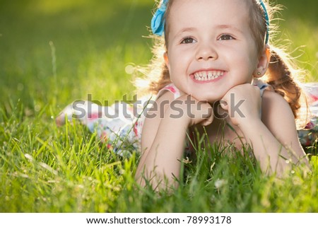 A cheerful little girl is lying on the green grass - stock photo