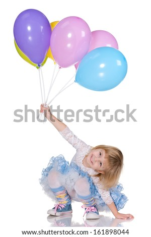 A cheerful little girl is playing with balloons on the white background - stock photo