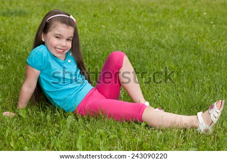A cheerful little girl is resting on the green grass in summer - stock photo