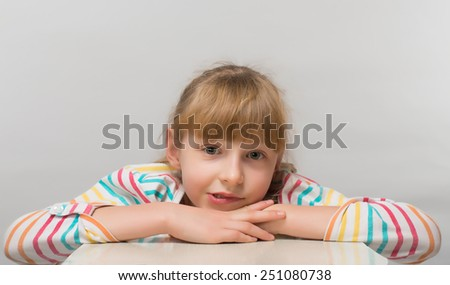 A cheerful little girl with funny tails is lying on the white carpet; isolated on the white background - stock photo