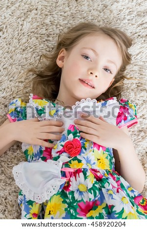 A cheerful little girl with funny tails is lying on the white carpet. Isolated on the white background - stock photo