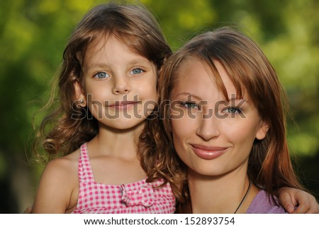 A cheerful little girl with her mother are in the park - stock photo