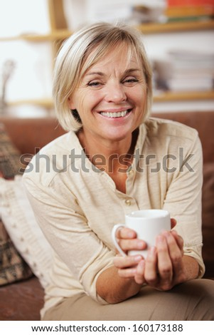 A cheerful senior woman enjoying a cup of coffee  - stock photo