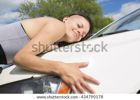 A Cheerful young female driver hugging her new car - stock photo