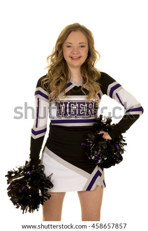 A cheerleader with down syndrome smiling at the camera.