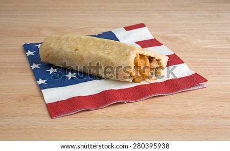 A cheese and chicken chimichanga that has been bitten on a flag motif napkin atop a wood table top. - stock photo