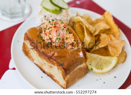 A cheese, prawn, seafood and tomato brioche sandwich, served with crisps and a wedge of lemon.