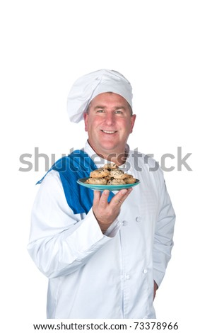 A chef holds up a plate of freshly baked cookies.