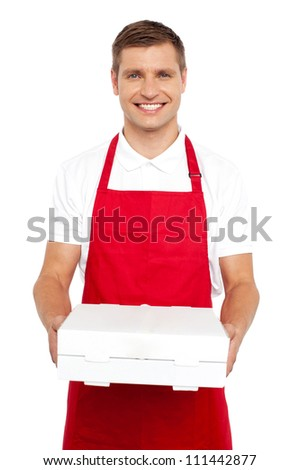 A chef in red uniform offering you a pizza box. Smiling at camera