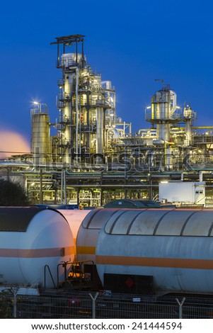 A chemical plant and refinery with night blue sky and illumination, some freight trains in the foreground. - stock photo