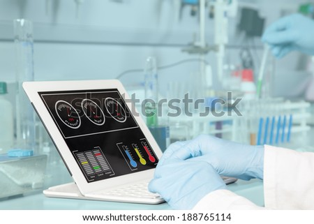 A chemist is analyzing the dashboard on his tablet pc. - stock photo