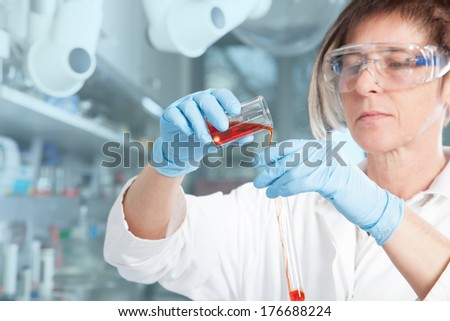A Chemist is decanting a red Liquid into a large test tube. - stock photo