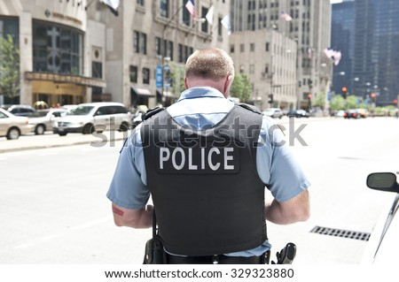 A Chicago city policeman standing on the road on a sunny day wearing a bullet proof vest mentioning Police on his body. On the background, cars and tall buildings are seen. - stock photo