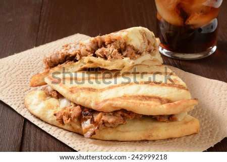 A chicken tikka sandwich on naan bread with a soft drink