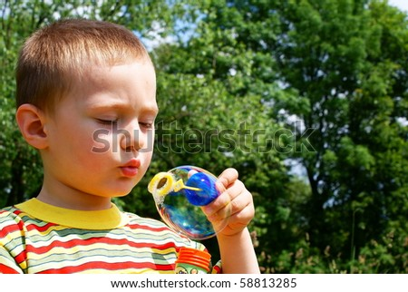 A child blowing bubble, background tree - stock photo