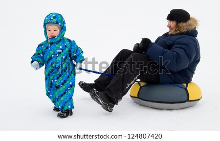... carries on dad tubing (inflatable sled). winter. Russia - stock photo