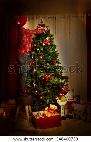A child decorates the Christmas tree