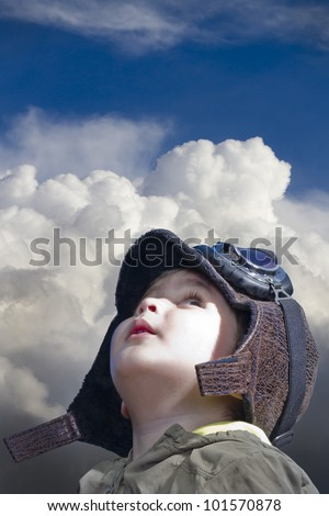 A child dressed in pilot looking into the blue sky - stock photo