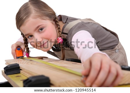 a child girl measuring a plank - stock photo