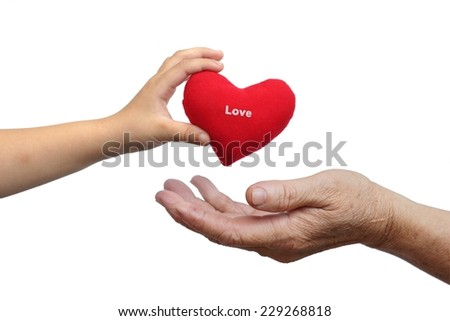 a child giving a red heart with the word love to an old female hand                       - stock photo