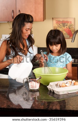 a child helper her mother in the kitchen - stock photo